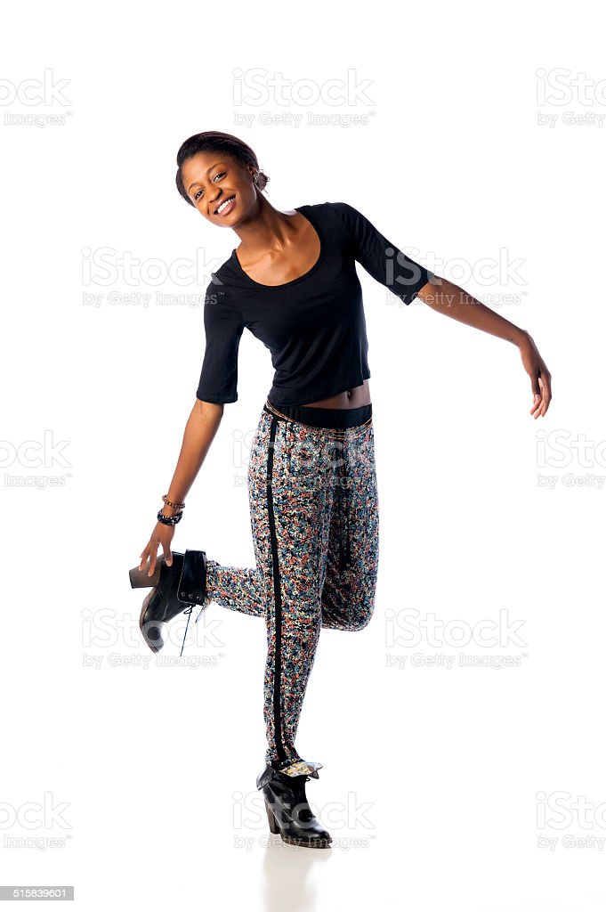 Happy Young Woman Standing on One Foot on White Background stock photo