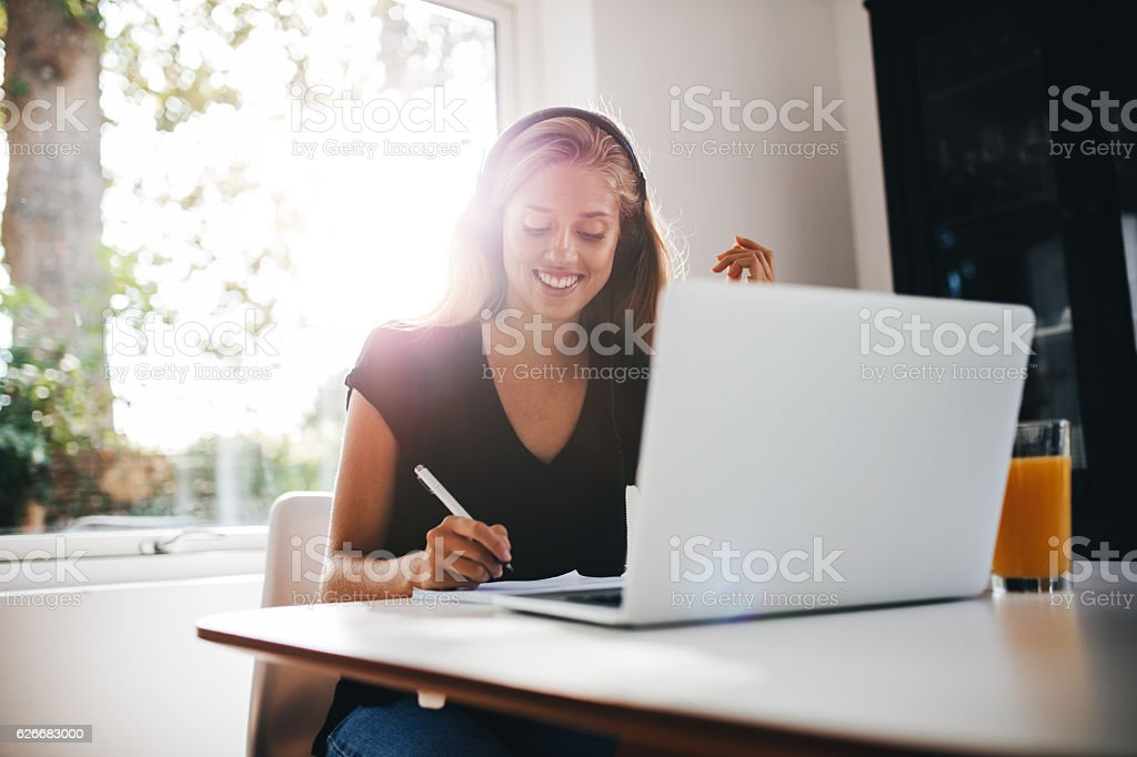 Happy young woman studying in kitchen stock photo