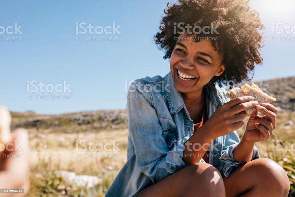 Happy young woman taking break during country hike. stock photo
