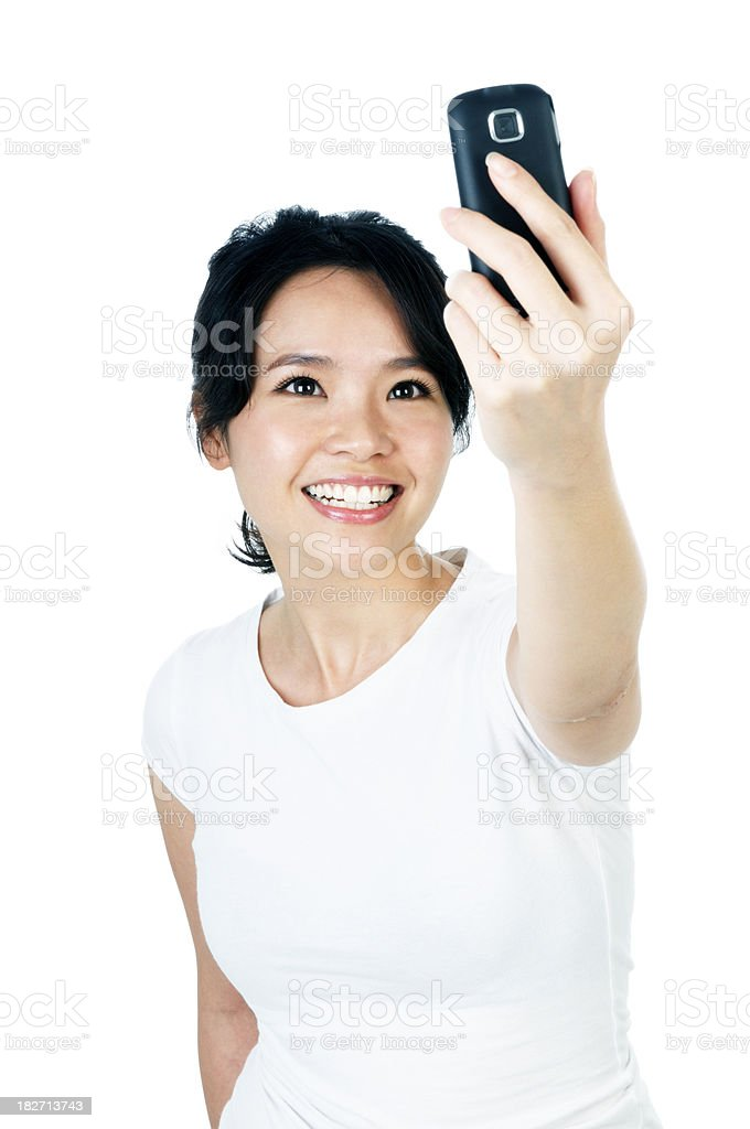 Happy young woman taking photograph with camera phone royalty-free stock photo