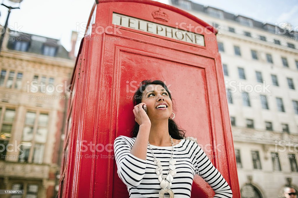 Happy Young Woman talking on mobile near phone booth stock photo