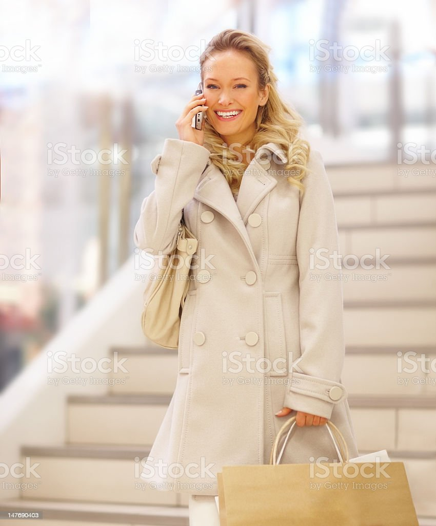 Happy young woman talking on mobile phone holding shopping bags royalty-free stock photo