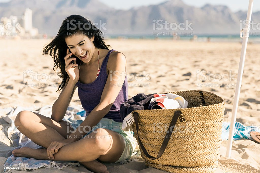 Happy young woman talking on phone at beach stock photo