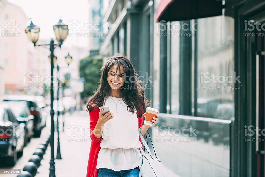 Happy young woman texting on the street stock photo