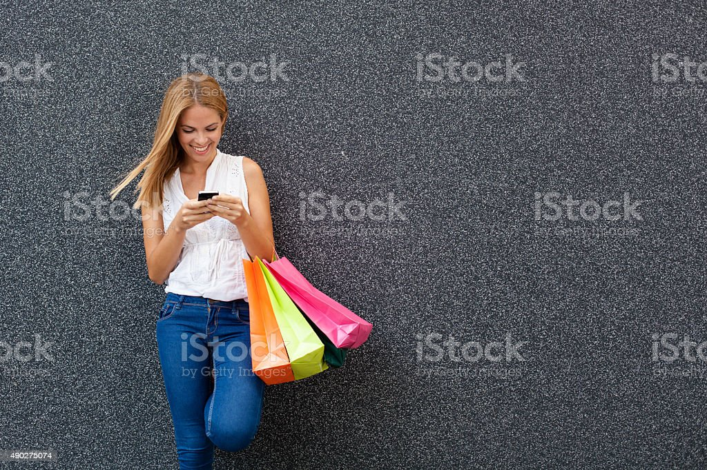 Happy young woman typing a message the phone after shopping stock photo