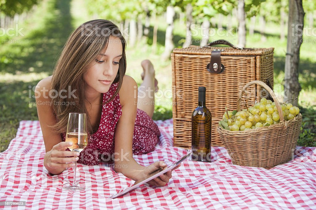 Happy young woman use tablet to a picnic royalty-free stock photo
