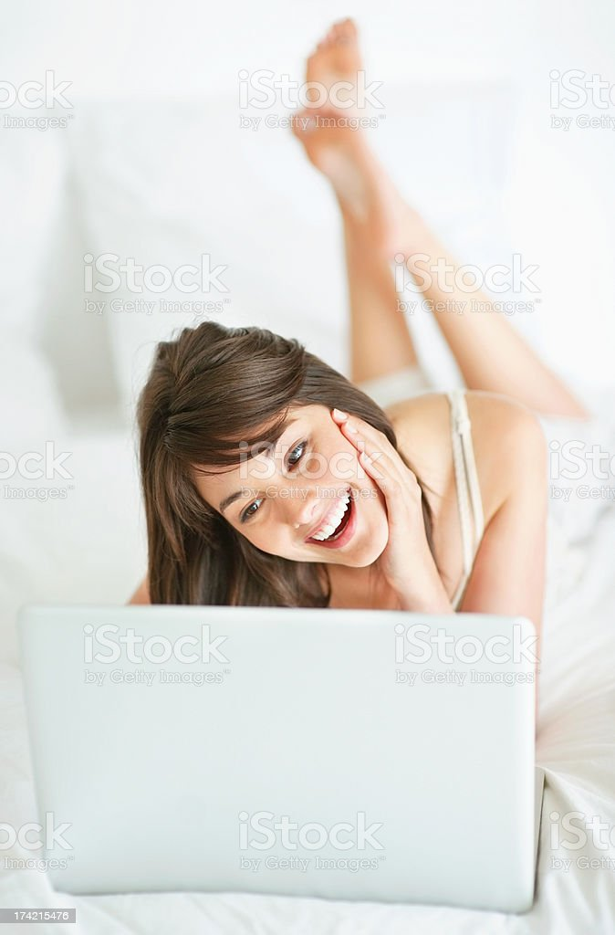 Happy young woman using a laptop at home stock photo