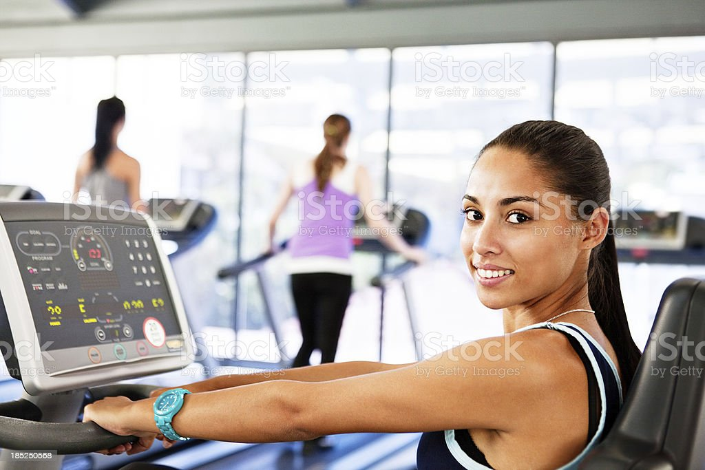 Happy young woman using computerized exercise equipment in gym stock photo