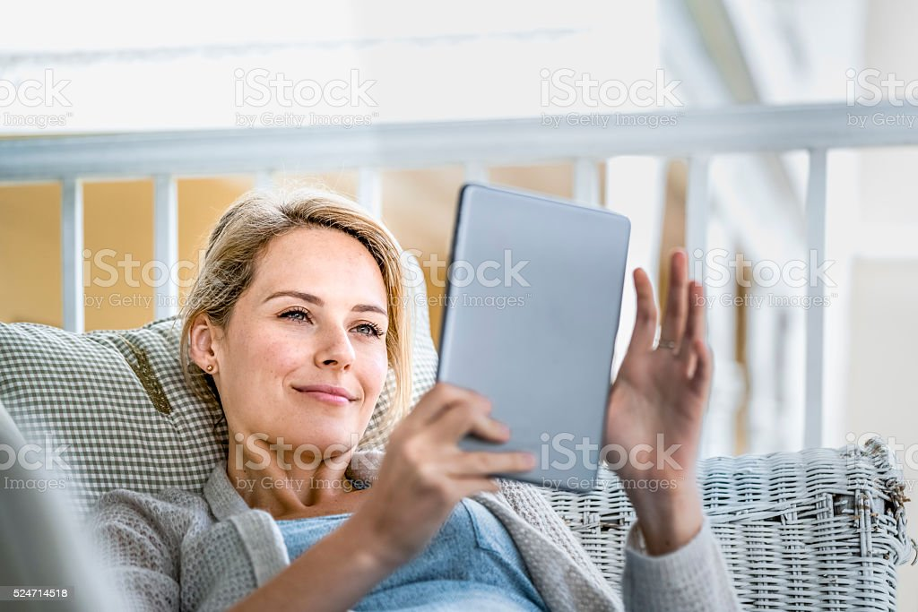 Happy young woman using digital tablet on balcony stock photo