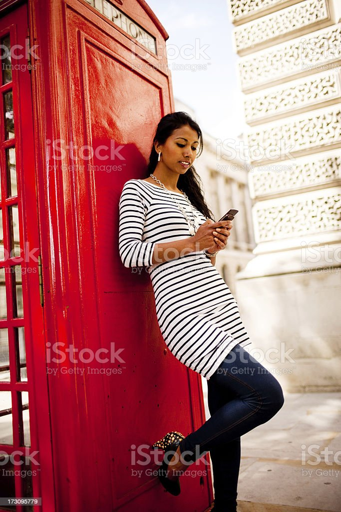 Happy Young Woman using her mobile near phone booth royalty-free stock photo