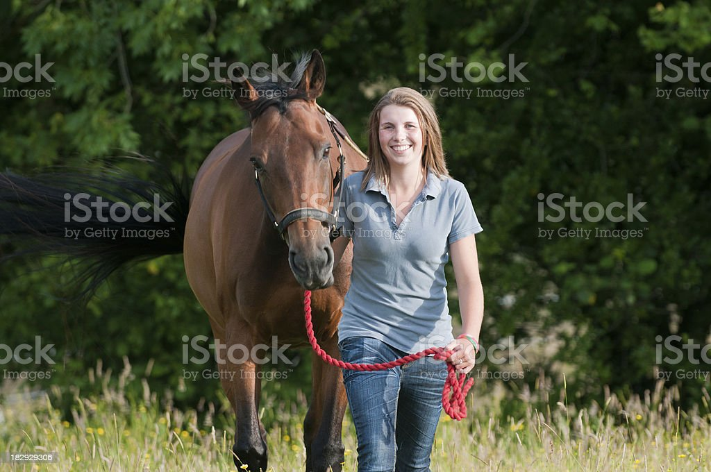 Happy young woman walking her horse stock photo