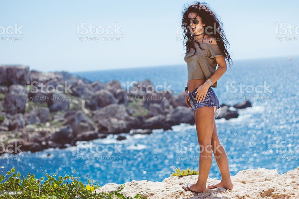 Happy young woman walking on island cliifs stock photo
