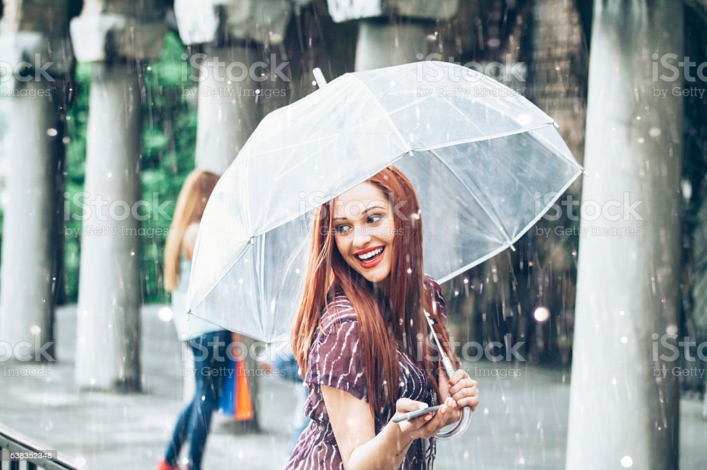 Happy young woman walking with umbrella under the rain stock photo