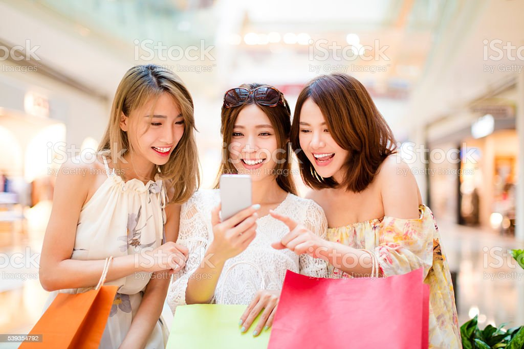 happy young woman  watching smart phone in shopping mall stock photo