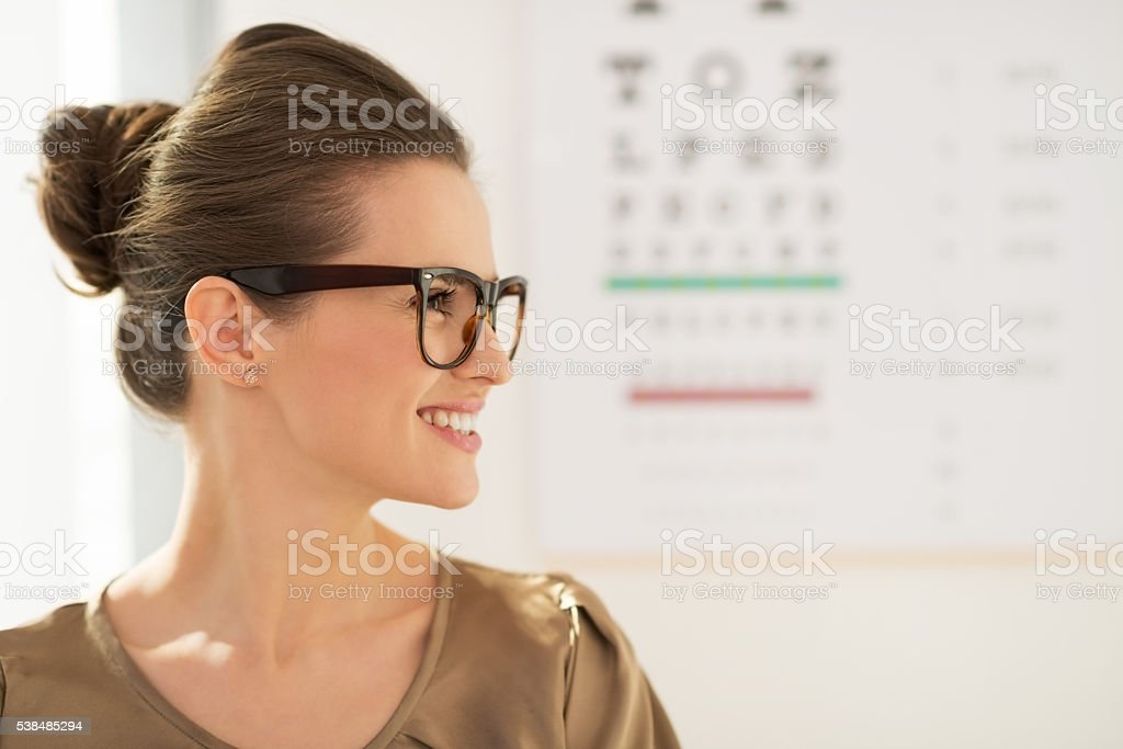 Happy young woman wearing eyeglasses in front of Snellen chart stock photo