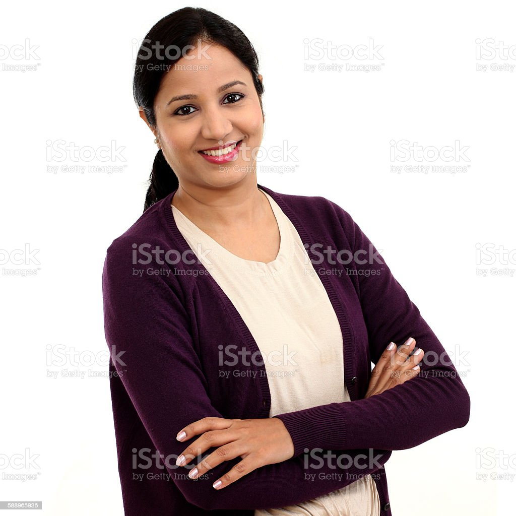 Happy young woman with arms crossed against white stock photo