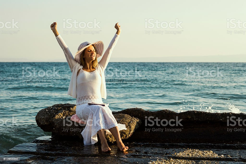 Happy young woman with book during beach vacation stock photo
