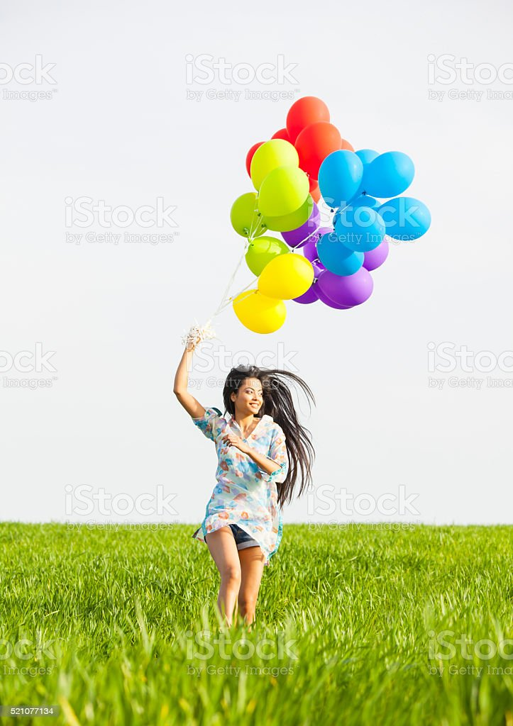 Happy young woman with brunch of balloons running in grassland stock photo