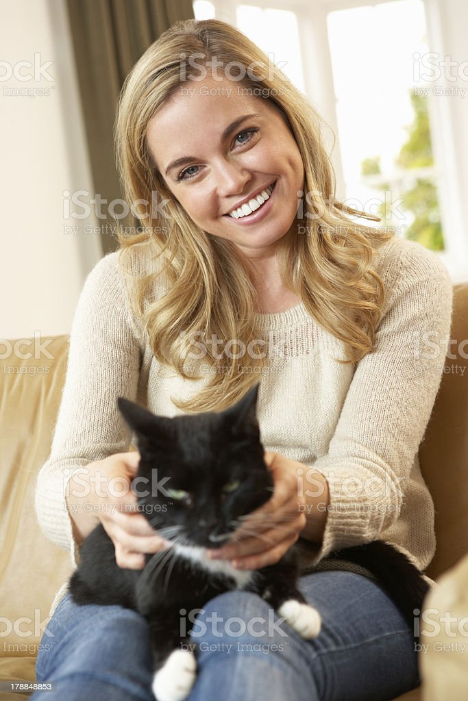 Happy young woman with cat sitting on sofa royalty-free stock photo