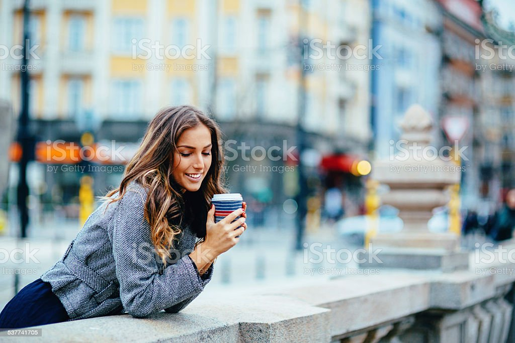Happy young woman with coffee cup outdoors stock photo