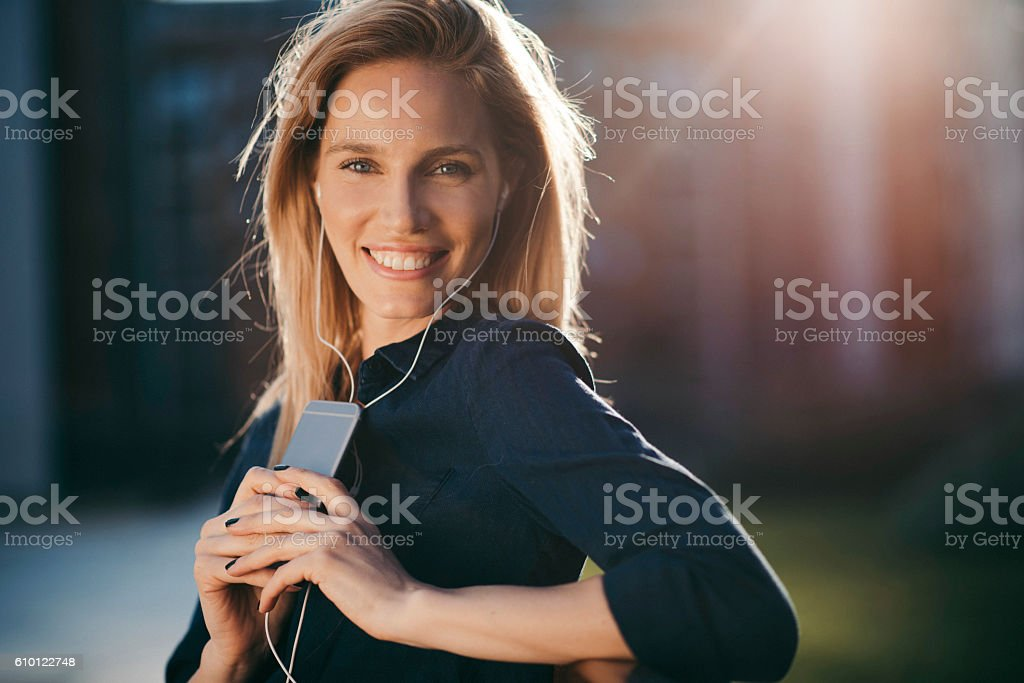 Happy young woman with headphones enjoying the day stock photo