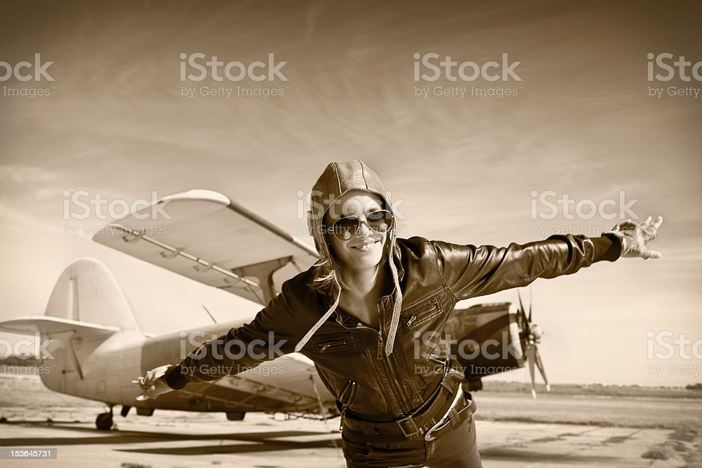 Happy young woman with raised hands  flying on airporte, stock photo