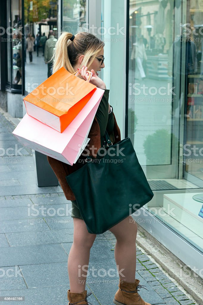 happy young woman with shopping bags in shop window stock photo