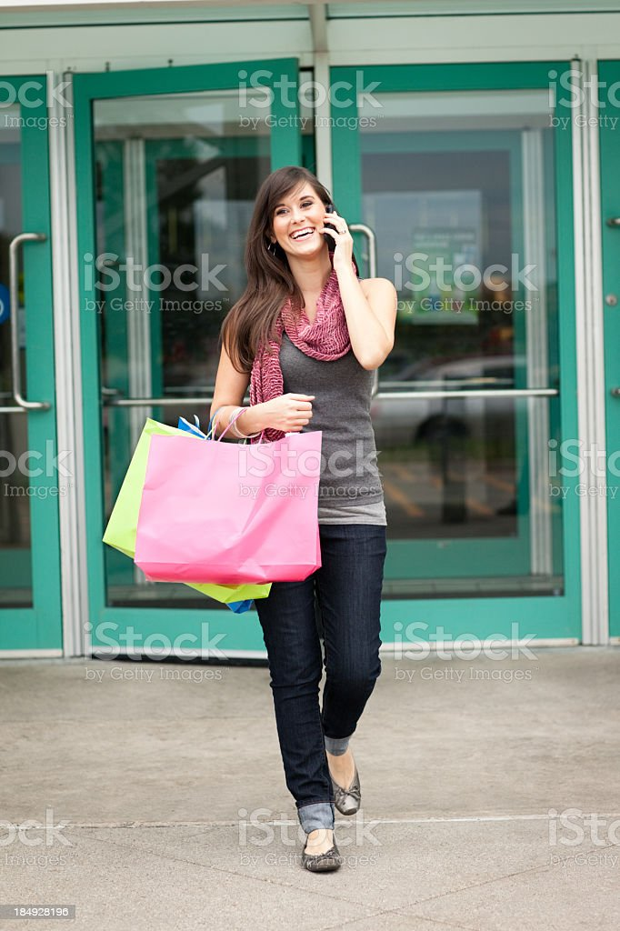 Happy Young Woman with Shopping Bags Leaving Mall royalty-free stock photo