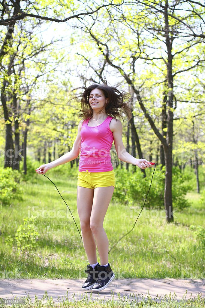 Happy young woman with skipping rope at summer park royalty-free stock photo