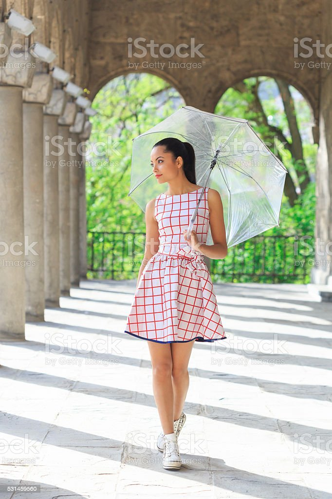 Happy young woman with umbrella walking under colonade stock photo