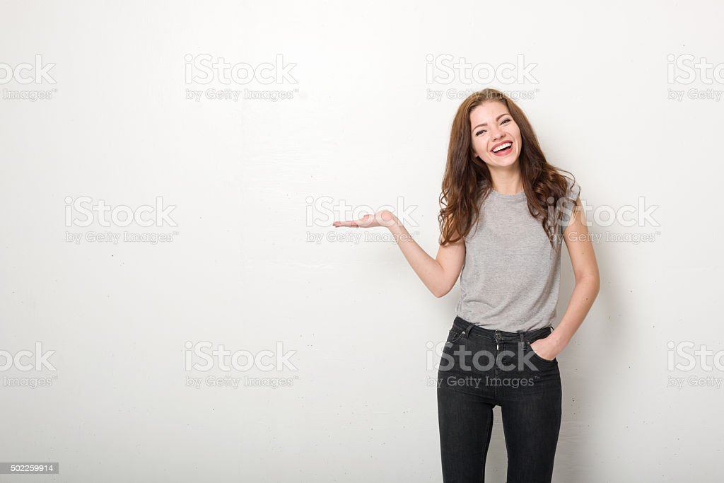 Happy Young Woman with White Wall and Casual Clothing stock photo