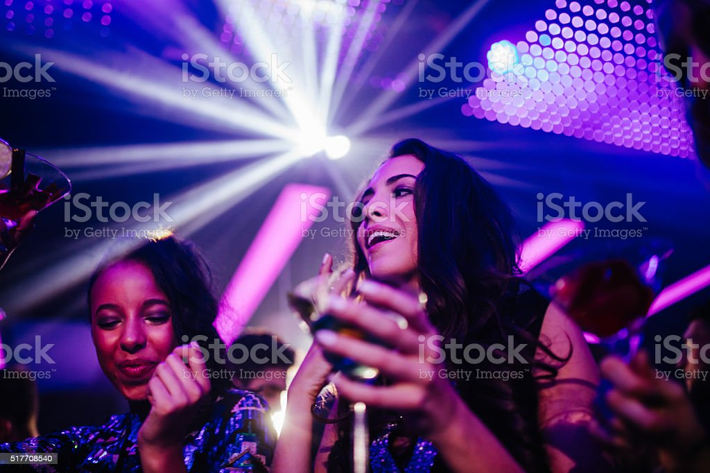 Happy young women drinking cocktail in night club party stock photo