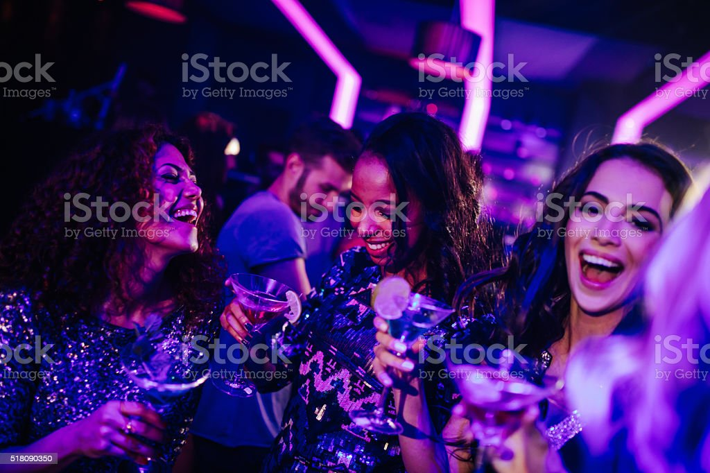 Happy young women enjoying cocktail in night club party stock photo