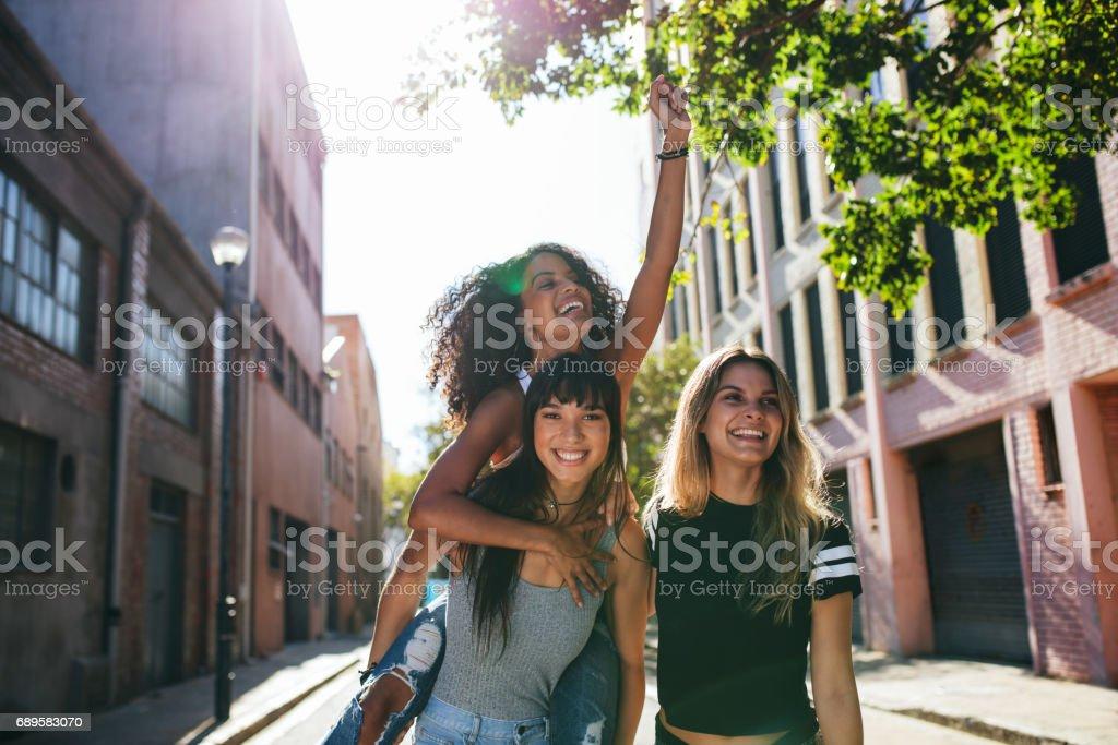 Happy young women enjoying on city street stock photo