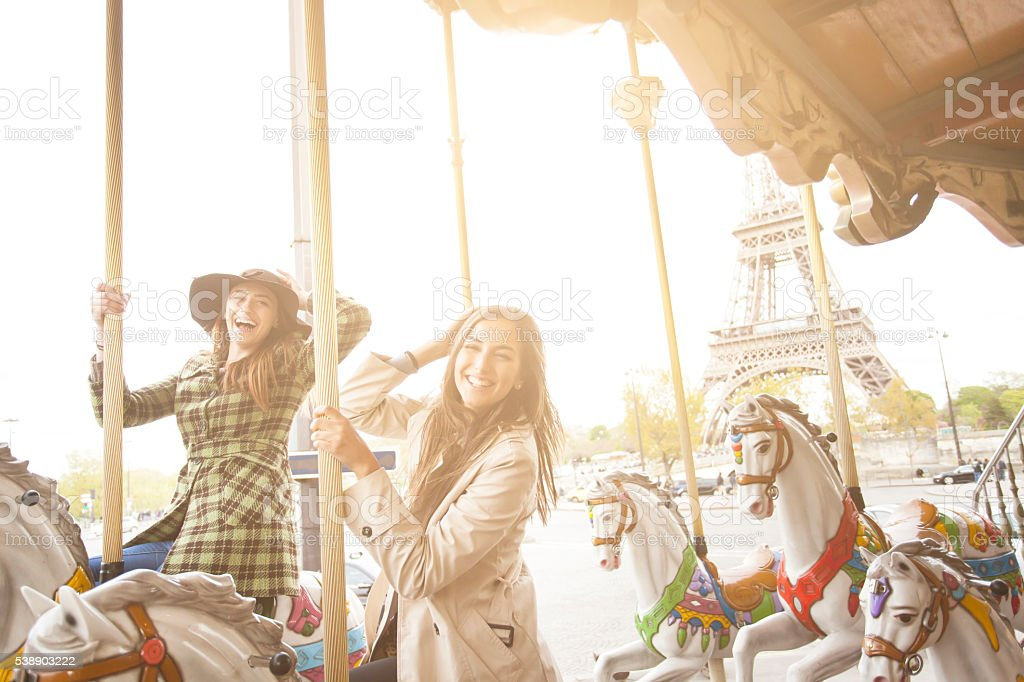 Happy young women having fun on carousel at Eiffel tower stock photo
