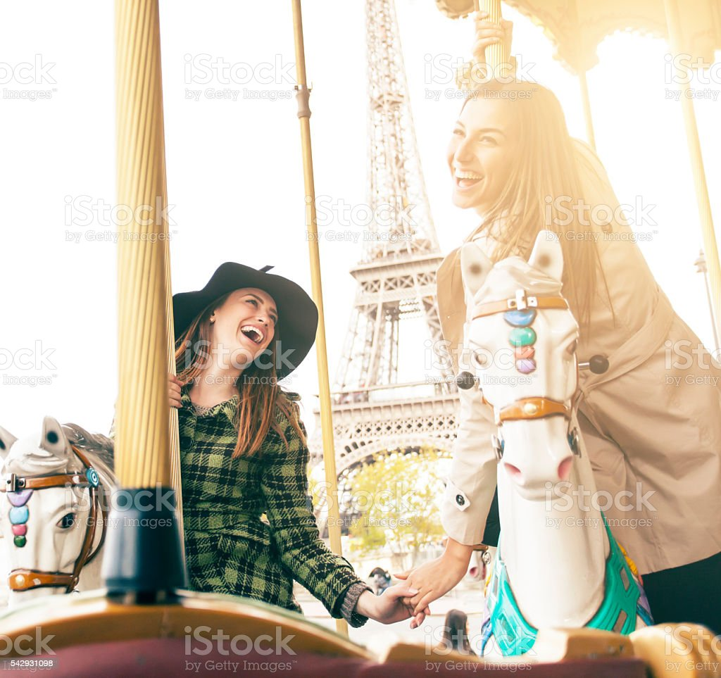 Happy young women having fun on marry-go-round at Eiffel Tower stock photo