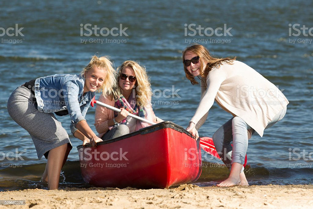 Happy young women having fun with a canoe stock photo