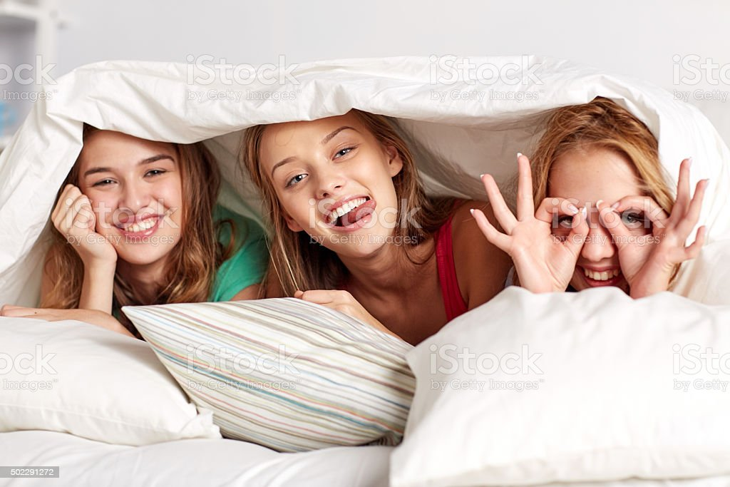 happy young women in bed at home pajama party stock photo