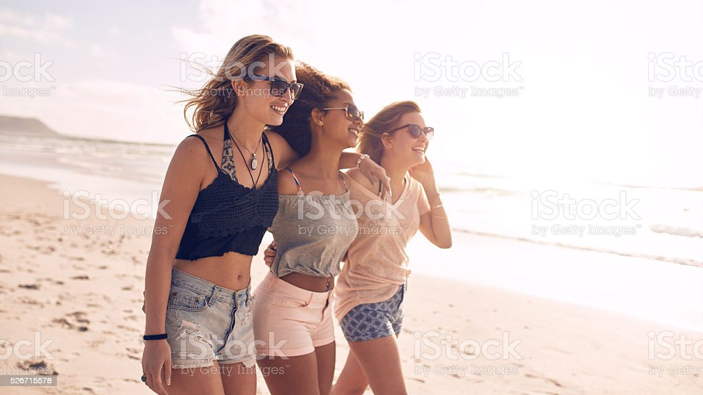 Happy young women strolling along coastline stock photo