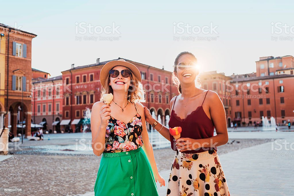 happy young women walking and eating ice cream stock photo