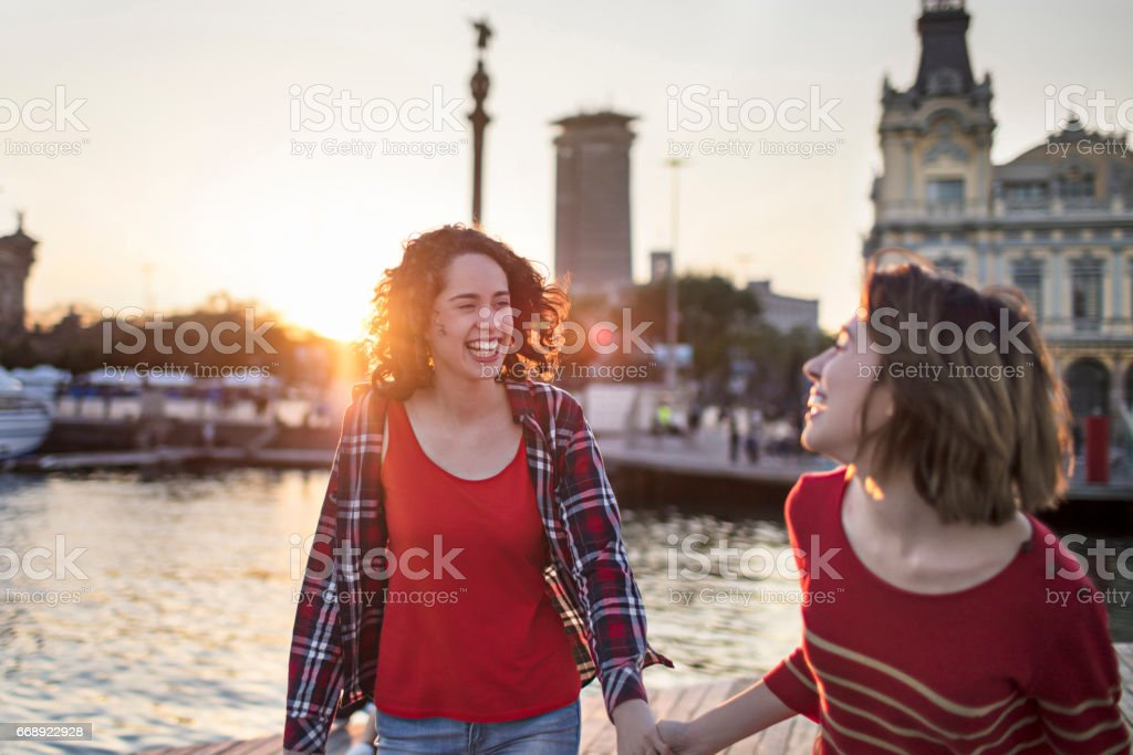 Happy young women walking at harbor in city stock photo