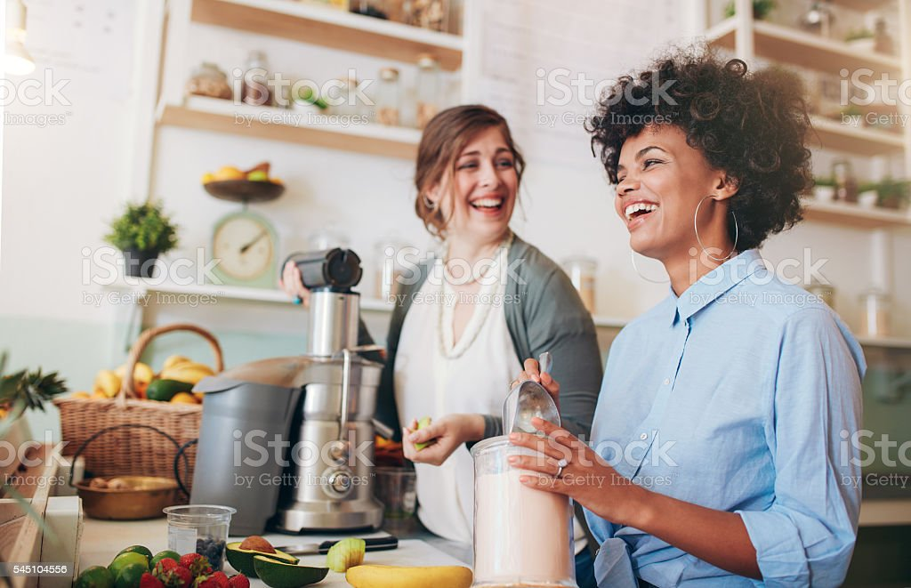 Happy young women working at juice bar counter stock photo