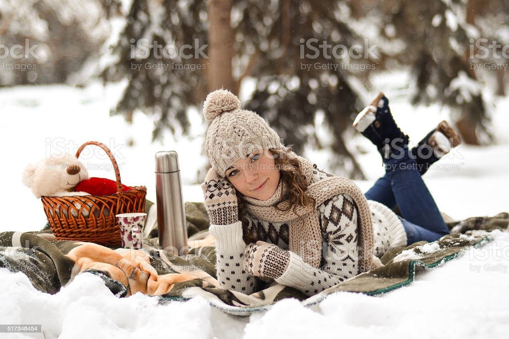 Happy,cute girl lay, relax on plaid in winter park stock photo