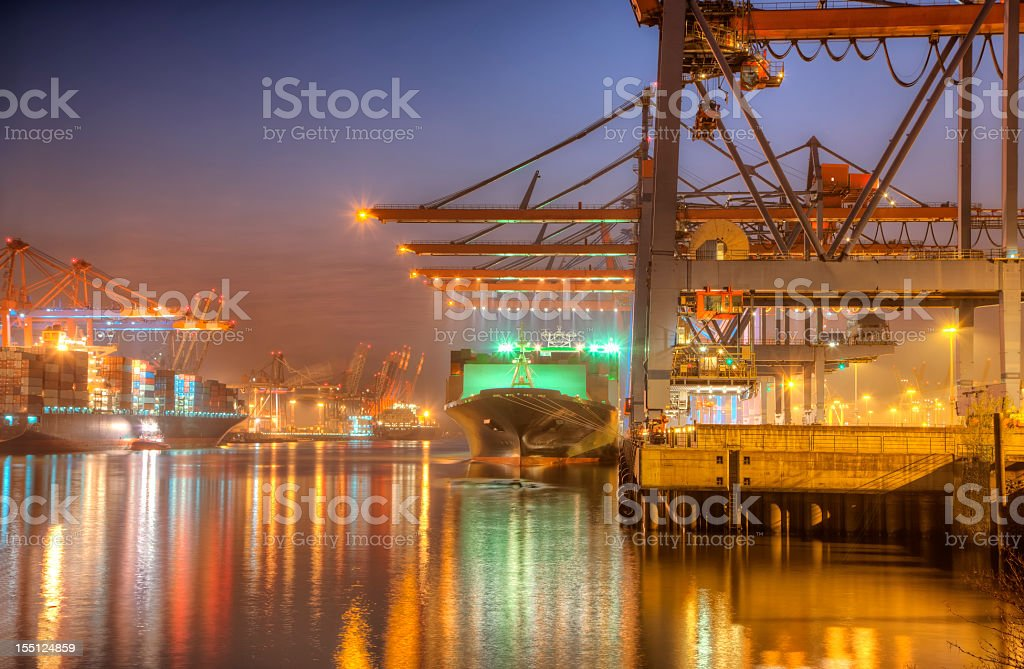 Harbor at sunrise with ships, cargo, and colorful lights  stock photo