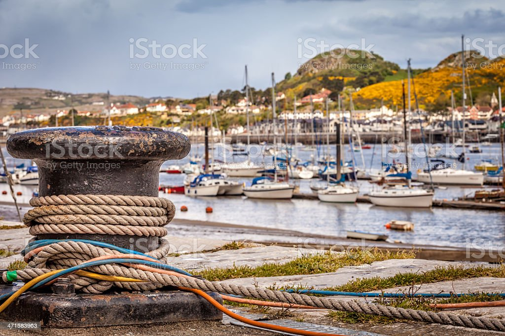 Harbor bollard with mooring ropes and colorful cables royalty-free stock photo