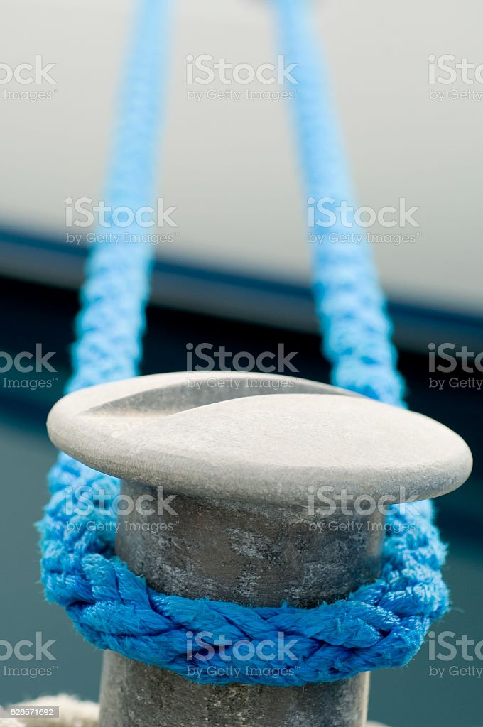 Harbor mooring post and thick ropes. stock photo