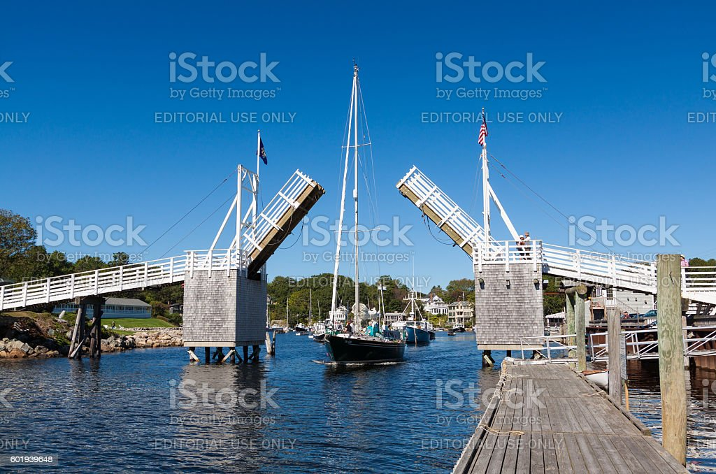 Harbor View with Sailboat Passing Under Drawbridge, Perkins Cove, Maine. stock photo