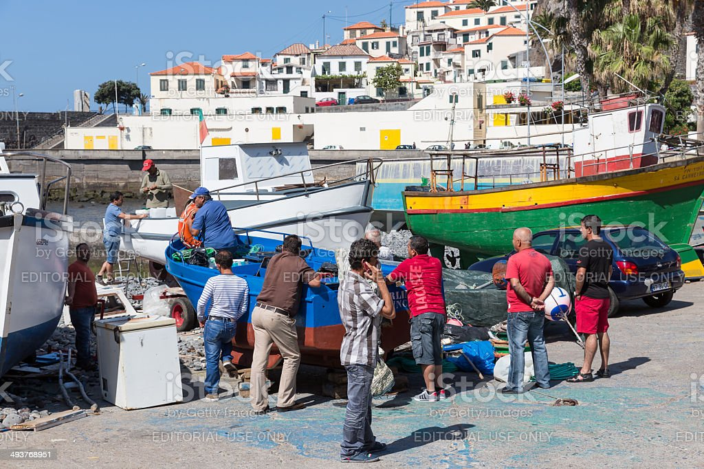 Harbor with fishermen and fishing ships in Funchal, Portugal stock photo