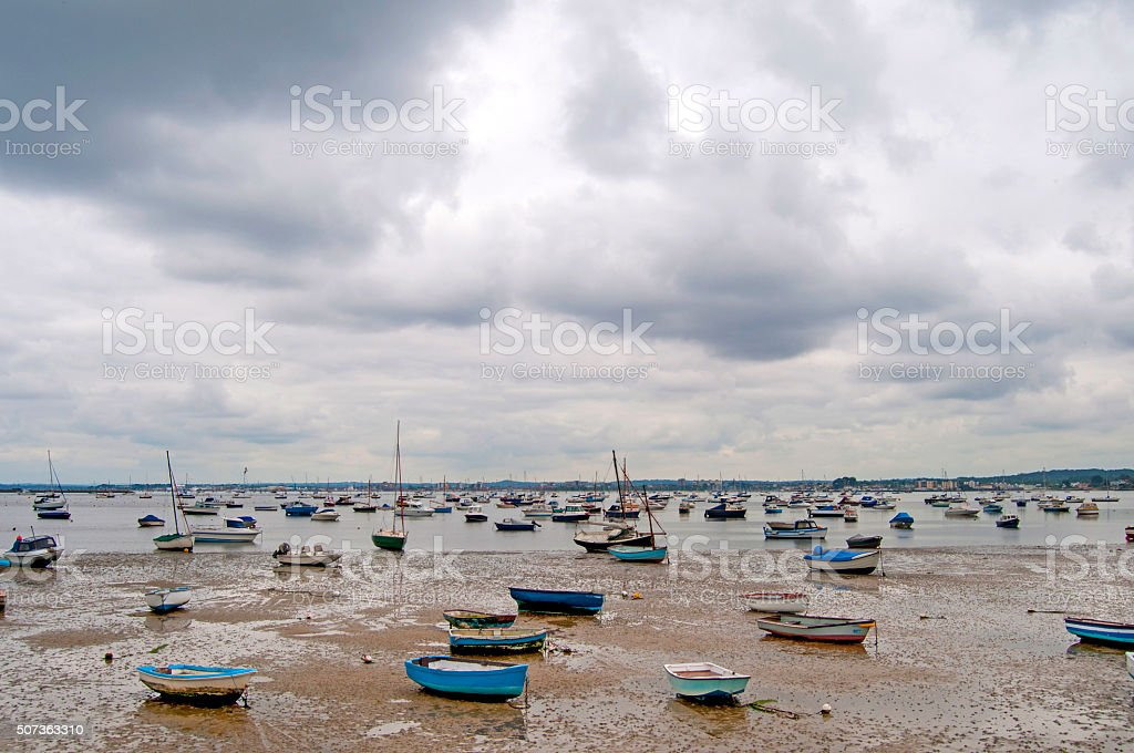Harbour at low tide with boats on shore stock photo