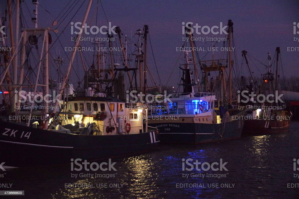 Harbour at night with fishing boats stock photo